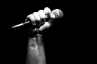 Gray Scale Microphone in Fist Against Black
