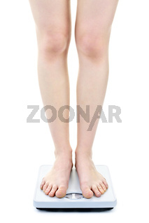 Woman standing on bathroom scale