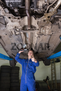 Male mechanic under car gesturing thumbs up