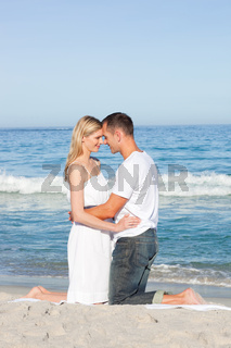 Enamoured couple kissing at the shore line
