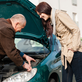 Man working on repairing a woman's car