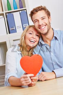 Paar hält rotes Herz im Wohnzimmer