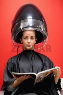 Portrait of a cute woman under a hairdressing machine