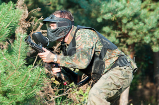 paintball player with gun and camouflage uniform