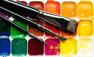 Watercolor paintbox and paintbrushes close-up