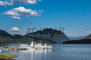 Landscape of mountain lake with the ship