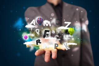 Young businessman presenting magical clouds with letters and balloons concept