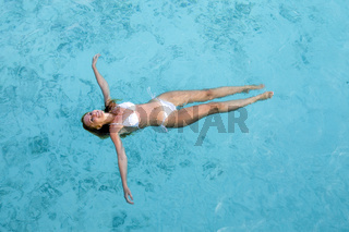 Young pretty woman smiles lying down on ocean surface.