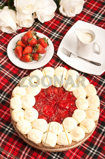 sweet round baked cake with strawberries on red
