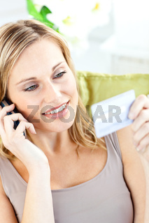 Beautiful young woman holding a card and phoning lying a sofa