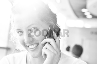young woman is talking phone and looking at camera