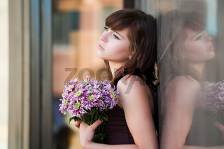 Sad young woman with a flowers