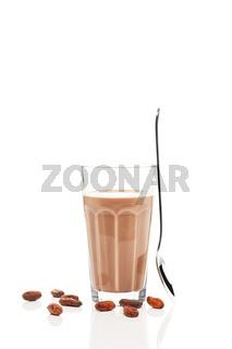 schokoladen milch mit stehendem löffel und schokoladenbohnen