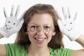 Schadenfrohe junge Dame mit Smiley Handschuhen