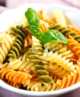 Spiral pasta in bowl with basil