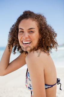 Young woman wearing a bikini while smiling and standing on the beach