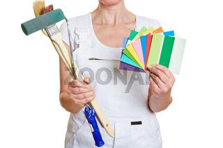 Frau in Malerkleidung mit Farbfächer und Pinsel