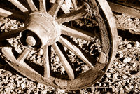 Part of an old wagon wheel close-up. Sepia