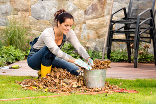 Smiling woman stuffing leaves pail autumn gardening