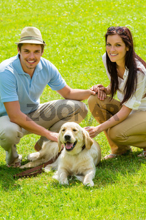 Young happy couple with Labrador dog