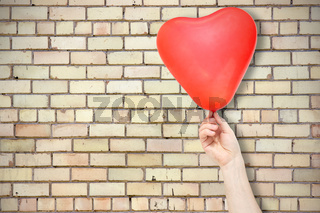 Brick wall and hand with balloon