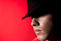 Handsome man portrait hat dark eyes mistery concept red background