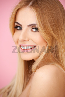 Smiling blond young woman over pink
