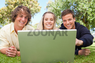 Portrait of three happy students in a park