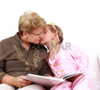 Cute little girl reading with grandmother and giving a kiss