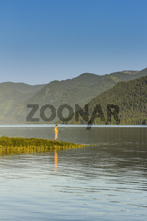 One fisherman on the bank of reservoir in mountains