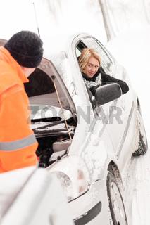 Man repairing woman's car snow assistance winter