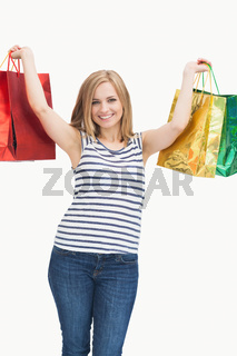 Portrait of cute excited young woman holding up shopping bags