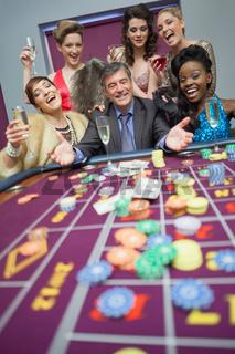 Women celebrating man's success at roulette