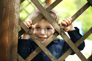 little funny boy behind the fence