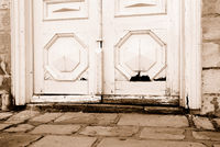 Lower part of an old wooden door in stone house. Sepia