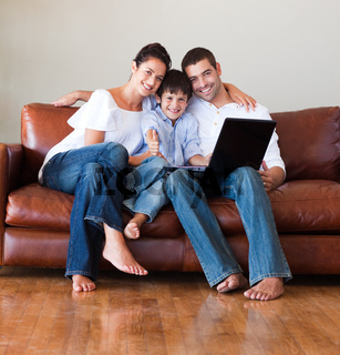 Parents and kid using a laptop with thumbs up