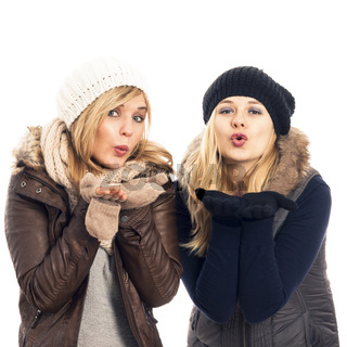 Happy women in winter clothes sending kiss