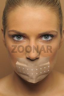 Junge Frau mit Pflaster über dem Mund