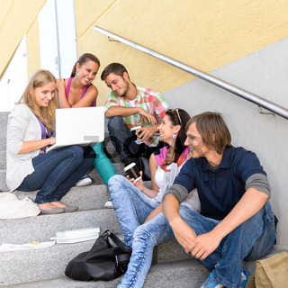 Students enjoying break on school steps laptop