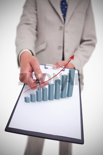 Businessman holding clipboard with graph hologram