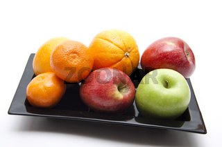 Orangen mit Äpfel auf schwarzen Teller