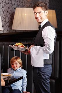 Kellner serviert Salat im Restaurant