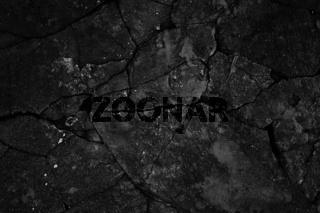 Black cracked concrete texture closeup background.