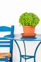 Blue chair and table with basil flowerpot