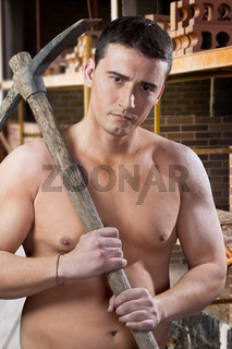 Young worker with pick axe and bricks