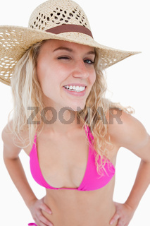 A smiling young woman blinking an eye