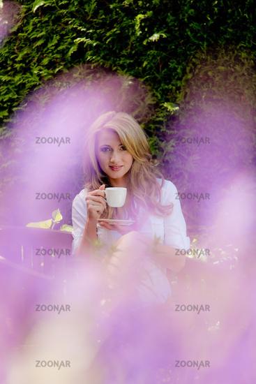 Frau trinkt Kaffee zum Frühstück in Garten