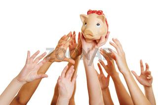 Hände greifen nach Geld im Sparschwein