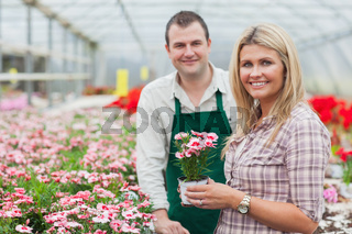 Smiling woman holding flower pot with employee