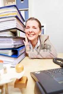 Frau im Büro mit Stapel voller Akten